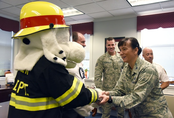 U.S. Air Force Col. Debra Lovette, 81st Training Wing commander, greets Sparky the Fire Dog during the kickoff of Fire Prevention Week at the 81st TRW headquarters building on Keesler Air Force Base, Mississippi, Oct. 9, 2018. The week-long event includes fire drills, literature hand-outs and stove fire demonstrations around the base and concludes with an open house at the fire department Oct. 13. (U.S. Air Force photo by Kemberly Groue)
