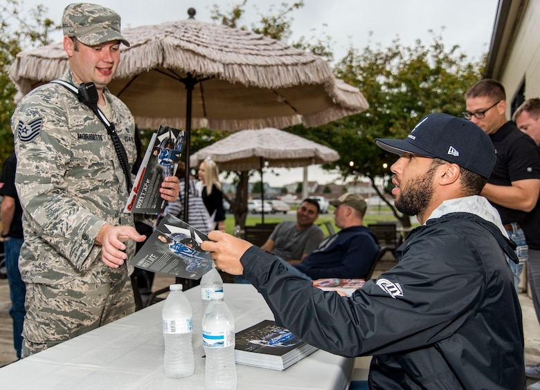 Bubba Wallace, driver of the No. 43 World Wide Technology Chevrolet in the Monster Energy NASCAR Cup Series, hands an autographed information card to Tech. Sgt. Scott Morisette, 436th Civil Engineer Squadron fire department station chief, during the NASCAR Social Oct. 5, 2018, at The Landings on Dover Air Force Base, Del. Wallace and several other NASCAR drivers visited the free event to meet with Team Dover members and show support for military families. (U.S. Air Force photo by Roland Balik)