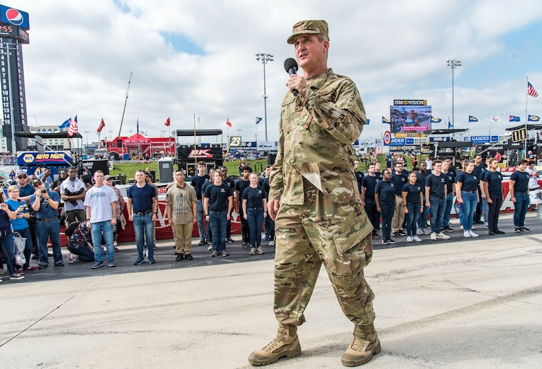 "Maj. Gen. Peter Gersten, U.S. Air Force Warfare Center commander, Nellis Air Force Base, Nev., speaks to race attendees before issuing the oath of enlistment for Air Force recruits and prior to the start of the ""Gander Outdoors 400"" Monster Energy NASCAR Cup Series race Oct. 7, 2018, at Dover International Speedway in Dover, Del. Forty-two recruits joined the U.S. Air Force, Delaware National Guard and Air National Guard through the Delayed Entry Program. Under the DEP, individuals going onto active duty, enlist first into the DEP. This is an actual enlistment into the inactive Reserves, with an agreement to report for active duty to attend basic military training at a specific time in the future. (U.S. Air Force photo by Roland Balik)"