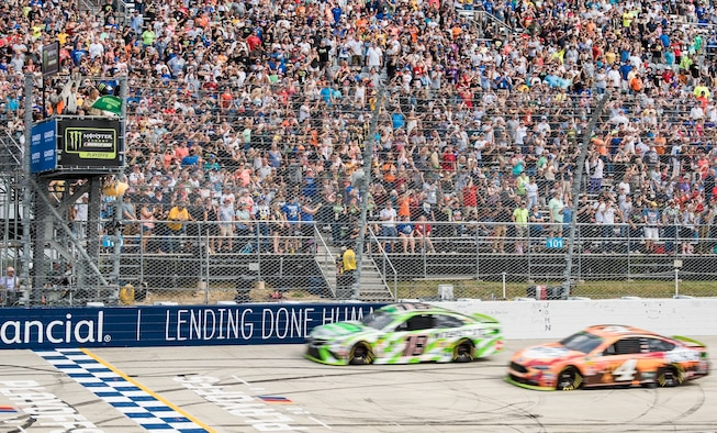 """Tech. Sgt. Michael Kelly (top left), 736th Aircraft Maintenance Squadron C-17 Globemaster III flight line expediter, waves the green flag for the start of the """"Gander Outdoors 400"""" Monster Energy NASCAR Cup Series race Oct. 7, 2018, at Dover International Speedway in Dover, Del. Kelly waved the flag as the row one cars, No. 18 Kyle Busch and No. 4 Kevin Harvick, head to the starting line. (U.S. Air Force photo by Roland Balik)"""