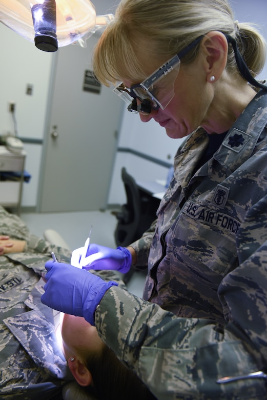 Lt. Col. Nicole Yingling, a dentist with the 193rd Special Operations Medical Group, Middletown, Pennsylvania, performs a routine checkup on an Airman Sept. 22, 2018. Yingling served 11 years as an active duty dentist and after a 12-year break-in-service, enlisted into the 193rd SOMDG. (U.S. Air National Guard photo by Senior Airman Julia Sorber/Released)