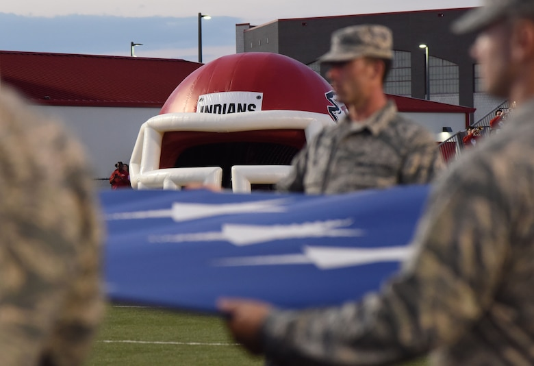 Keesler Airmen hold the U.S. Flag during the playing of the national anthem at the Biloxi High School military appreciation night football game in Biloxi, Mississippi, Oct. 5, 2018. Keesler personnel also participated in the coin toss to determine which team would receive the ball first. (U.S. Air Force photo by Kemberly Groue)