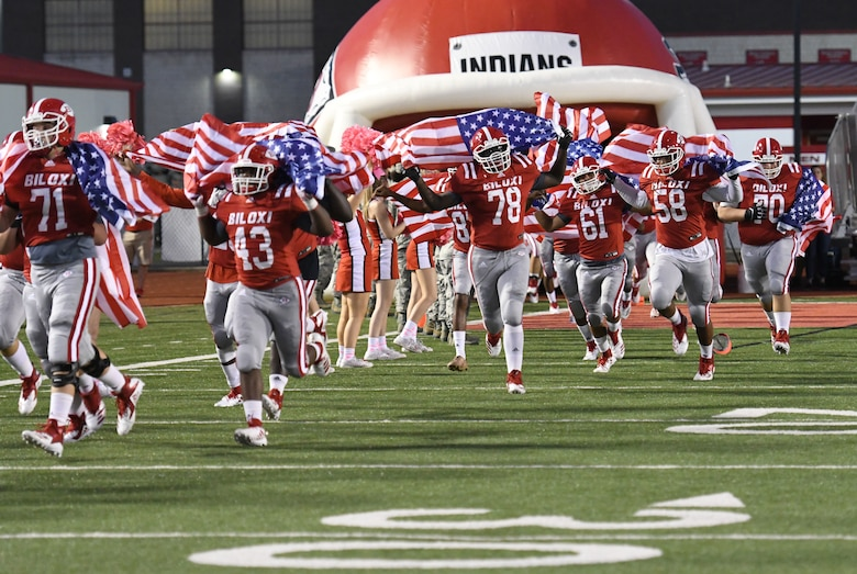 Members of the Biloxi High School Football Team run onto the field carrying U.S Flags during the Biloxi High School military appreciation night football game in Biloxi, Mississippi, Oct. 5, 2018. Keesler personnel also participated in holding the U.S. Flag during the playing of the national anthem and the coin toss to determine which team would receive the ball first. (U.S. Air Force photo by Kemberly Groue)