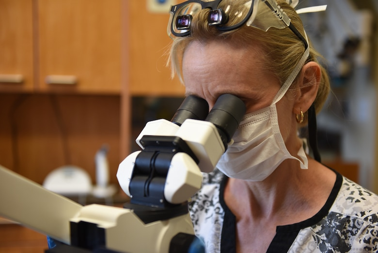 Dr. Nicole Yingling, endodontist and owner of Mason-Dixon Endodontics, Chambersburg, Pennsylvania, looks through an operating microscope to get a closer look at a cracked tooth Oct. 1, 2018. Yingling served 11 years as an active duty dentist and after a 12-year break-in-service, enlisted into the 193rd Special Operations Medical Group, Middletown, Pennsylvania. (U.S. Air National Guard photo by Senior Airman Julia Sorber/Released)