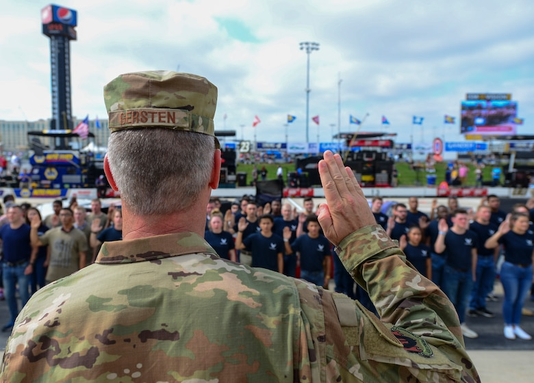 "Maj. Gen. Peter Gersten, U.S. Air Force Warfare Center commander, Nellis Air Force Base, Nev., administers the oath of enlistment for more than 40 enlistees in the Air Force Delayed Entry Program prior to the start of the ""Gander Outdoors 400"" Monster Energy NASCAR Cup Series race Oct. 7, 2018, at the Dover International Speedway in Dover, Del. This is one of the first steps these recruits will take to enter the United States Armed Forces. (U.S. Air Force photo by Airman First Class Dedan D. Dials)"