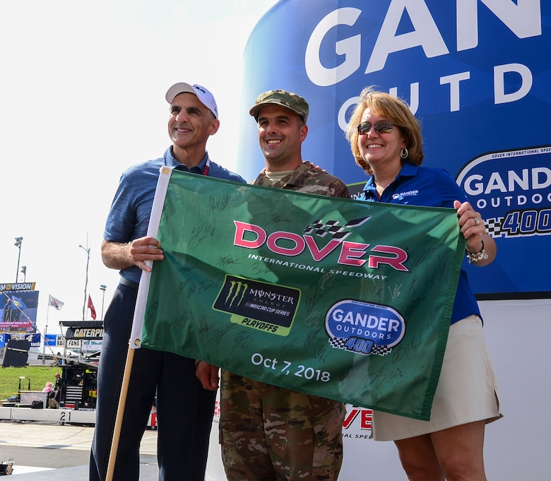 "Tech. Sgt. Michael Kelly, 736th Aircraft Maintenance Squadron, C-17 Globemaster III flight line expediter, receives the green flag from Mike Tatoian, Dover International Speedway president and CEO, and Tamara Ward, Camping World Holdings Inc. executive vice president of corporate development, at the ""Gander Outdoors 400"" Monster Energy NASCAR Cup Series race Oct. 7, 2018, at the Dover International Speedway in Dover, Del. Kelly was named the honorary starter for the race by DIS officials to honor his military service and to represent Dover Air Force Base at the event. (U.S. Air Force photo by Airman First Class Dedan D. Dials)"