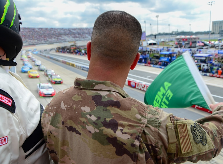 "Tech. Sgt. Michael Kelly, 736th Aircraft Maintenance Squadron, C-17 Globemaster III flightline expediter, waves the green flag at the start of the ""Gander Outdoors 400"" Monster Energy NASCAR Cup Series race Oct. 7, 2018, at the Dover International Speedway in Dover, Del. Kelly was selected for this honor on behalf of the NASCAR and DIS track officials to honor his military service and represented Dover Air Force Base in front of hundreds of thousands of viewers on national television. (U.S. Air Force photo by Airman First Class Dedan D. Dials)"