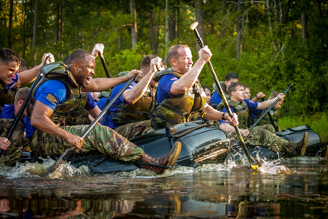 Paratroopers paddle rubber boats across a pond.
