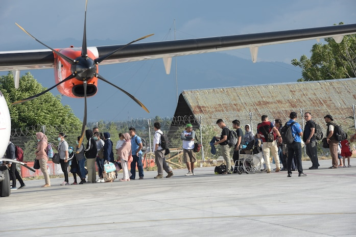 Evacuees prepare to board aircraft in Palu, Indonesia Oct. 6, 2018 after thousands were displaced after a 7.5 magnitude earthquake and tsunami struck Indonesia's Sulawesi Island Sept. 28, 2018. The Indonesian Government and U.S. Agency for International Development are working alongside eight countries agencies and foreign militaries ensuring supplies, airlift, shelter and medical support reach those affected. (U.S. Air Force photo by Master Sgt. JT May III)