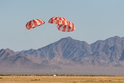 An Orion test capsule with its three main parachutes touches down in the Arizona desert Sept. 12, 2018. The evaluation was the final test to qualify Orion's parachute system for flights with astronauts. (U.S. Army photo)