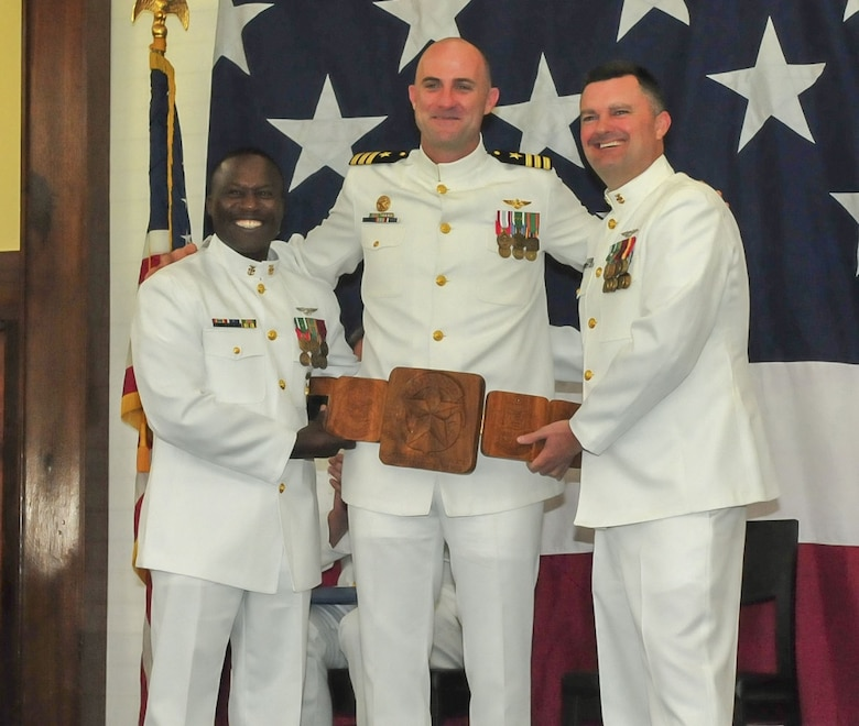 ANDERSEN AIR FORCE BASE, Guam (Oct. 5, 2018) – Helicopter Sea Combat Squadron 25 Command Master Chief Keith Wilkerson, left, and Master Chief Avionics Maintenance Technician John Adams, right, present a plaque to commanding officer Cmdr. William Eastham during the HSC-25 change of command ceremony at the Sunrise Conference Center at Andersen Air Force Base Oct. 5. During the ceremony, Cmdr. Frank Loforti relieved Eastham as commanding officer. (U.S. Navy photo by Alana Chargualaf)