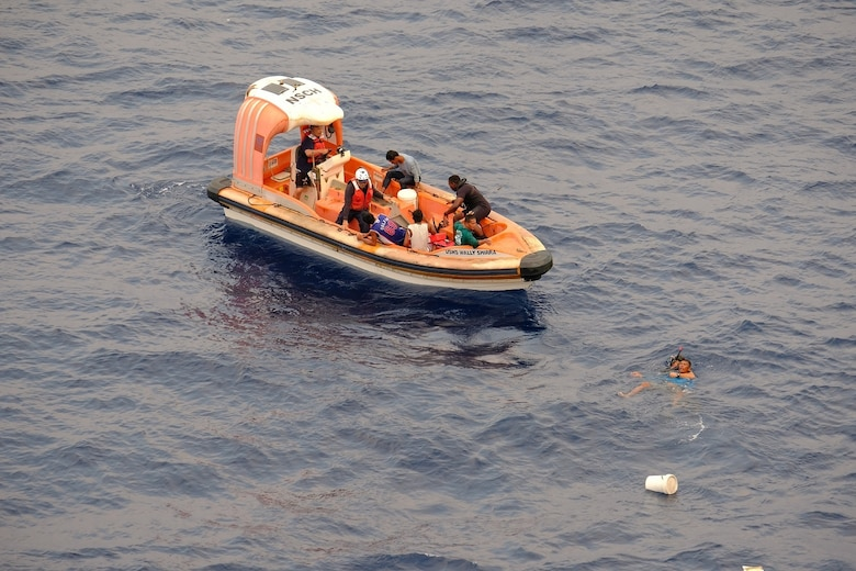 SOUTH CHINA SEA—A search and rescue swimmer from USNS Wally Schirra (T-AKE 8) rescues a fisherman off an adrift and distressed boat in the South China Sea, Oct. 8. Five Filipino fishermen survived for five days aboard a makeshift boat after their fishing boat sank at sea and they were rescued by the crew of USNS Wally Schirra.