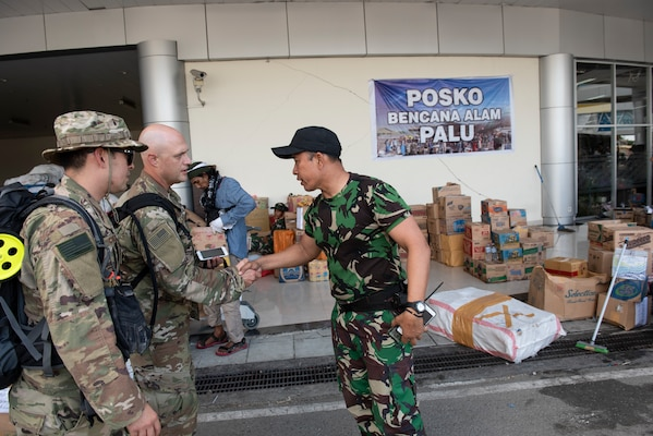 U.S. Air Force Lt. Col. Aaron Lane, 36th Mobility Readiness Squadron commander, Maj. Sean Conley, 36th MRS operations officer, both assigned to the 36th Contingency Response Group Andersen Air Force Base, Guam, are greeted by an Indonesian military member in Palu, Indonesia Oct. 6, 2018. The purpose of the visit was to establish an initial baseline of how to best support our Indonesian counterparts. (U.S. Air Force photo by Master Sgt. JT May III)