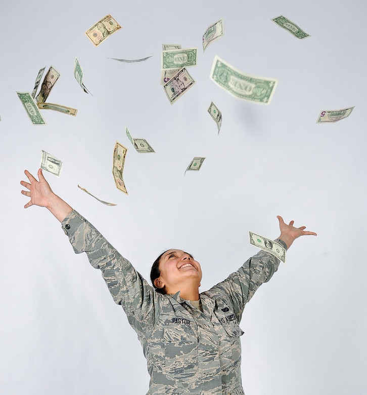 Airman 1st Class Daniela Pastor, 86th Airlift Wing Judge Advocate paralegal, throws money into the air on Ramstein Air Base, April 7, 2017. The Cost of Living Allowance (COLA) Living Pattern Survey (LPS) for Germany will be available on-line from 1 October through 31 October 2018.. (U.S. Air Force photo by Senior Airman Savannah L. Waters)