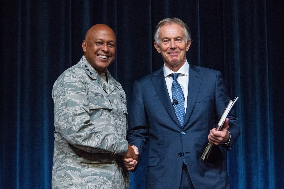 Lt. Gen. Anthony Cotton, Air University commander and president, presents a token of appreciation to former British Prime Minister Tony Blair for taking time to speak with the students of AU, Oct. 5, 2018, Maxwell Air Force Base, Ala. Blair received an illustrative history book about the Tuskegee Airmen, one of the major historical contributions made to aviation that took place here in Alabama. (U.S. Air Force photo by Melanie Cox.)