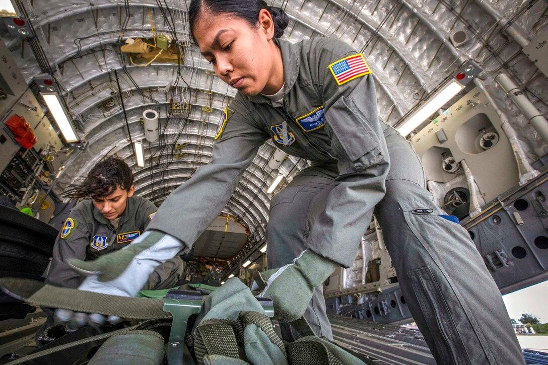 Two airmen strap down equipment aboard an aircraft.