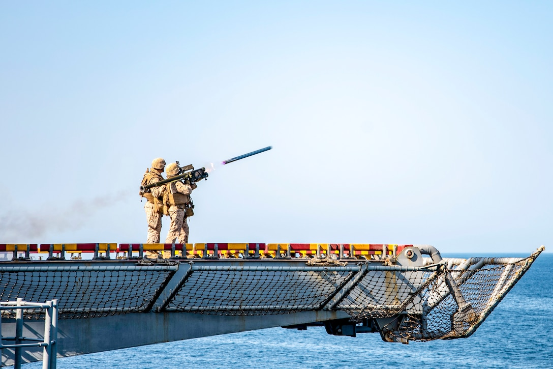 Two Marines fire a missile from a ship's flight deck over water.