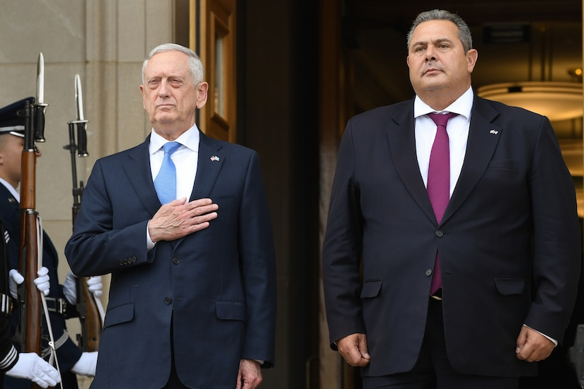 U.S. and Greek defense leaders stand at attention at the top of the Pentagon steps.