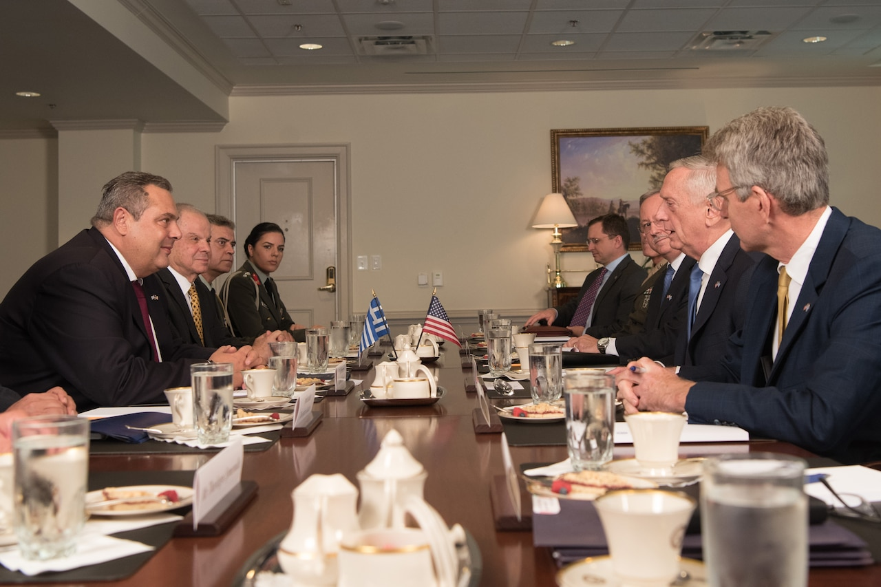Defense leaders meet at a table at the Pentagon.