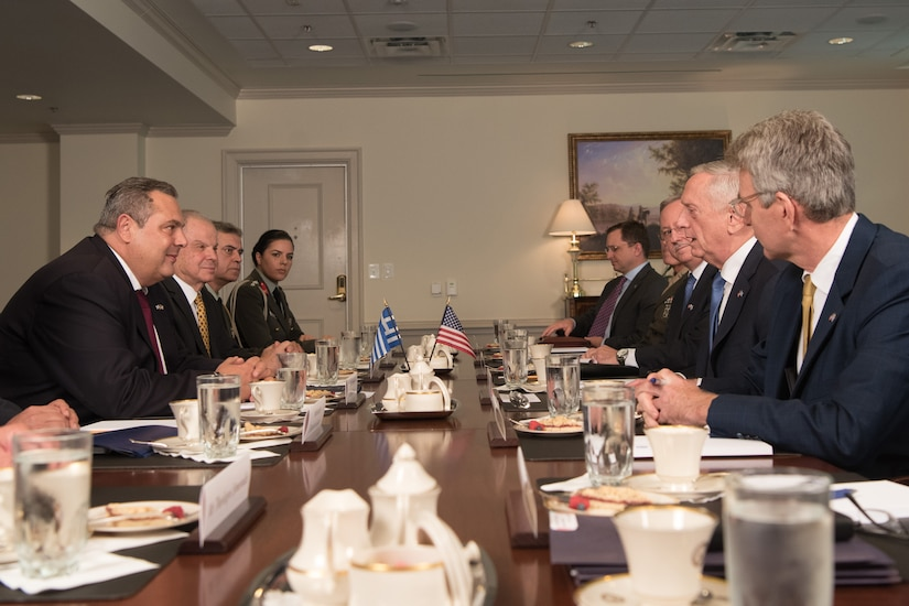 Defense leaders meet at a table at the Pentagon.