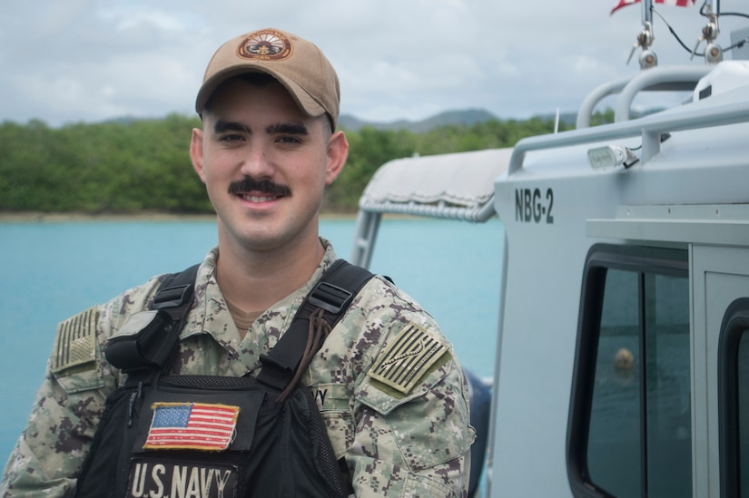 A Navy petty officer poses in front of a boat.