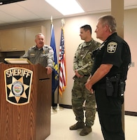 Ken Wenger, left, Milford Lake park manager, presented Geary Co. Sheriff's Deputy Rick Parsons and Pfc. Chance Harriss, stationed at Fort Riley, Kan., with 'Act of Heroism' awards at the Geary County Sheriff's Office October 9, 2018.