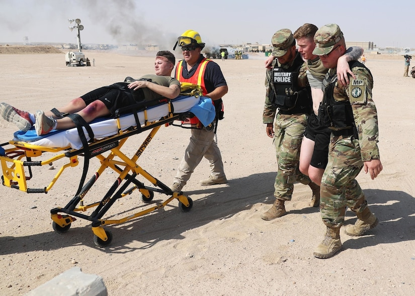 Military police and the Camp Buehring EMS personnel assist injured Soldiers at Camp Buehring, Kuwait, during a Mass Casualty Training Exercise hosted by Area Support Group-Kuwait, September 26, 2018.