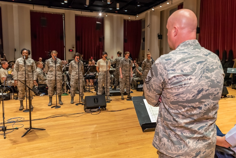 Members from the Singing Sergeants rehearse with the Concert Band while Non Commissioned Officer in Charge Senior Master Sgt. observes