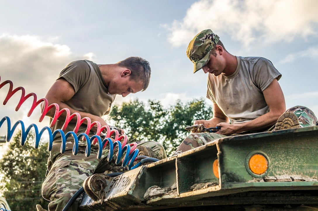 Two soldiers sit atop a green piece of equipment and look down at their work.