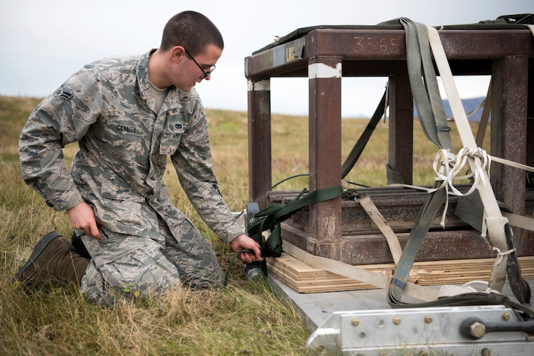 U.S. Air Force Airman 1st Class Robert Canales, a 773d Logistics Readiness Squadron combat mobility technician, secures a heavy air drop platform at the Joint Base Elmendorf-Richardson, Alaska, drop zone Oct. 3, 2018. When air drop training occurs, combat mobility technicians are called upon to operate as malfunction officers at the drop zone. In addition to scouting, technicians are also responsible to recover the loads using specific field-packing methods for secure transport back to the rigging facility.