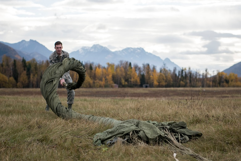 U.S. Air Force Senior Airman David Throckmorton, a 773d Logistics Readiness Squadron combat mobility technician, cigar-rolls a G-12 cargo parachute at the Joint Base Elmendorf-Richardson, Alaska, drop zone Oct. 3, 2018. When air drop training occurs, combat mobility technicians are called upon to operate as malfunction officers at the drop zone. In addition to scouting, technicians are also responsible to recover the loads and parachutes using specific packing methods to keep them from getting torn or ripped.
