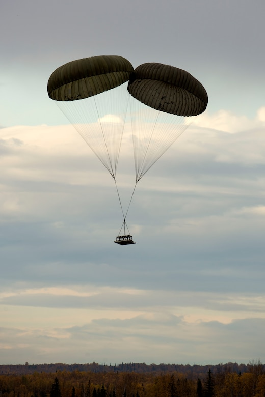 A heavy drop platform falls from the sky during air drop qualification training at Joint Base Elmendorf-Richardson, Alaska, Oct. 3, 2018. Two G-12 cargo parachutes were used for this heavy load weighing 3,700 pounds. When air drop training occurs, combat mobility technicians from the 773d Logistics Readiness Squadron are called upon to operate as malfunction officers at the drop zone.