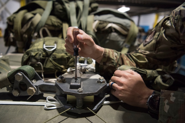 U.S. Air Force Staff Sgt. Douglas Moye, a 773d Logistics Readiness Squadron combat mobility technician supervisor, checks an M-1 parachute release timing block used for heavy cargo platform parachutes at Joint Base Elmendorf-Richardson, Alaska, Oct. 3, 2018. An arming wire sets the timing blocks off, once the timer hits zero it releases the parachute connector links from the M-1 parachute release system. This allows the main parachutes to separate from the load.