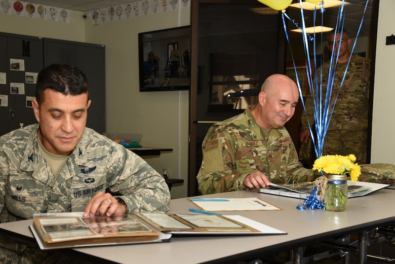 U.S. Air Force Col. Ricky Mills, 17th Training Wing commander, and Col. Robert Ramirez, 17th TRW vice commander, look through scrapbooks at the one-year anniversary event of the STARBASE program at the STARBASE facility on Goodfellow Air Force Base, Texas, Oct. 10, 2018. The program focuses on teaching fifth graders about science, technology, engineering and math career fields. (U.S. Air Force photo by Staff Sgt. Joshua Edwards/Released)