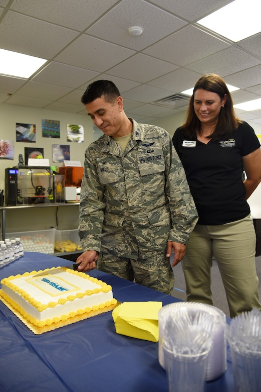 U.S. Air Force Col. Ricky Mills, 17th Training Wing commander, cuts a cake while STARBASE Director, Katheryn Ganster, watches during the one-year anniversary event of the STARBASE program at the STARBASE facility on Goodfellow Air Force Base, Texas, Oct. 10, 2018. All San Angelo Independent School District fifth-grade students participate in the STARBASE program. (U.S. Air Force photo by Staff Sgt. Joshua Edwards/Released)