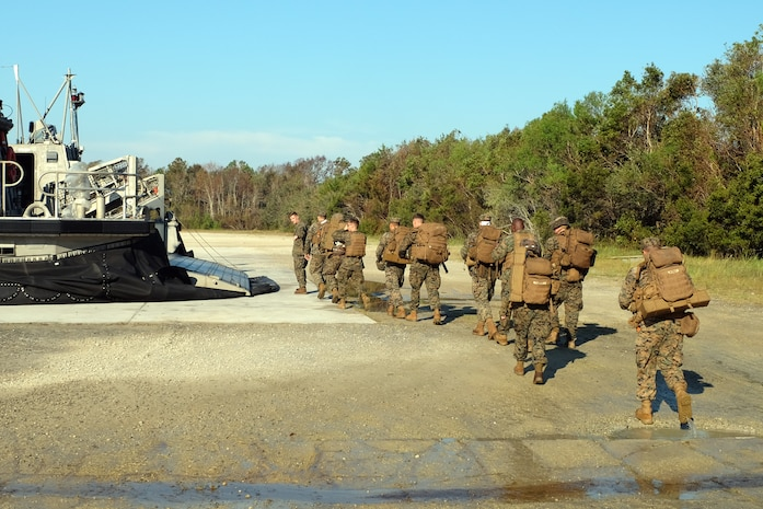 A U.S. Marines prepare to board a Landing Craft Air Cushion at Mile Hammock Bay, Camp Lejeune, North Carolina, Oct. 5, 2018 in preparation to embark aboard USS Iwo Jima (LHD 7) during Type Commander Amphibious Training. TCAT allows the 24th Marine Expeditionary Unit, their subordinate units, and the U.S. Navy's Iwo Jima Amphibious Ready Group to rehearse ship to shore maneuver and expeditionary command and control prior to exercise Trident Juncture 2018. The goal of TCAT is to increase unit and individual proficiency during amphibious operations. The LAVs are with 2nd Light Armored Reconnaissance Battalion, 24th Marine Expeditionary Unit.  (U.S. Marine Corps photo by Gunnery Sgt. Robert Durham/released)