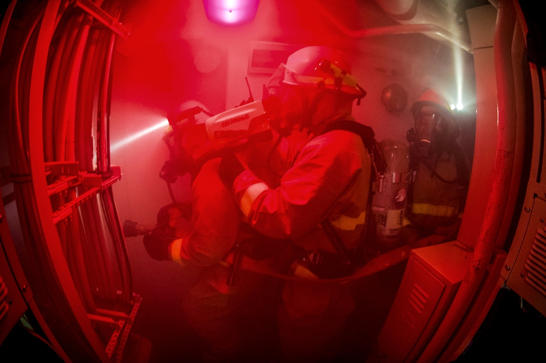 Three firefighters move through smoke wearing protective clothing on a Navy vessel