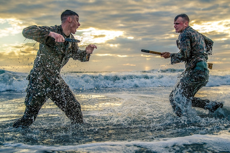 Two Marines spar along the edge of the water on a beach.