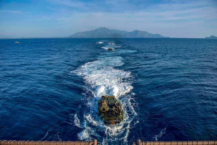Amphibious military vehicles make their way toward a ship in the sea.