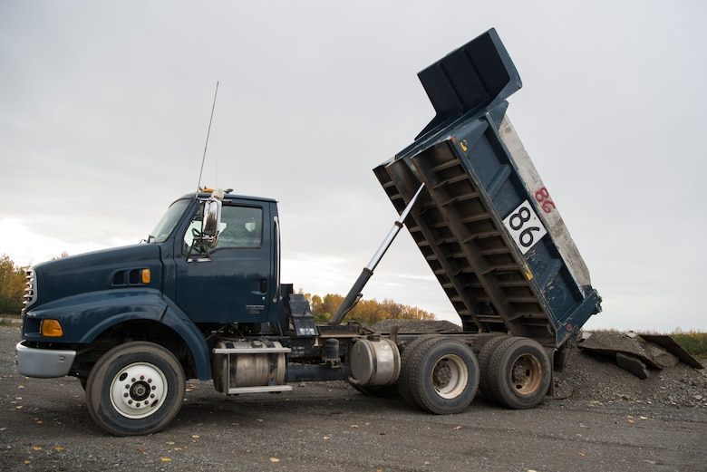 U.S. Air Force Airman 1st Class Shane Leaphart, 773d Civil Engineer Squadron engineer assistant, unloads a dump truck at Joint Base Elmendorf-Richardson, Alaska, Oct. 3, 2018. The 773d CES snow barn personnel train augmentees on properly operating snow-removal equipment, in preparation for the coming winter.