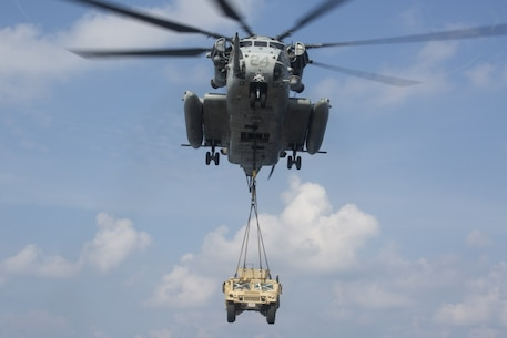 A CH-53E Super Stallion helicopter belonging to Marine Medium Tiltrotor Squadron 262 (Reinforced) lifts a Humvee during Helicopter Support Team training aboard the amphibious assault ship USS Wasp (LHD 1), underway in the South China Sea, Oct. 1, 2018.