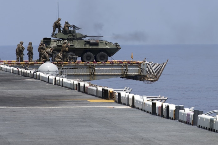 Marines with Weapons Company, Battalion Landing Team, 2nd Battalion, 5th Marines, sit on a Light Armored Vehicle atop the flight deck aboard the amphibious assault ship USS Wasp (LHD 1) during a defense of the amphibious task force drill, underway in the South China Sea, Sept. 27, 2018.