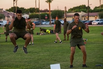 """Lt. Col. James C. Paxton III, the commanding officer of Headquarters and Headquarters Squadron (H&HS), conducts a """"squat jump"""" exercise beside another Marine during High Intensity Tactical Training (HITT) on the Lawn, at the parade deck on Marine Corps Air Station Yuma, Ariz., Sept. 28, 2018. HITT on the Lawn is a physical training event that is open to anyone with base access and provides them with a physical training opportunity. (U.S. Marine Corps photo taken by Cpl. Isaac D. Martinez)"""