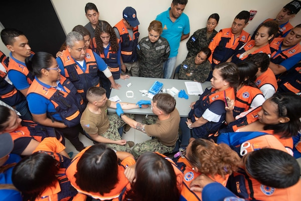U.S. Navy hospital corpsmen demonstrate proper intravenous application at a Comite Permanente de Contingencias (COPECO) facility as part of a subject matter expert exchange with Honduran emergency response medical personnel.