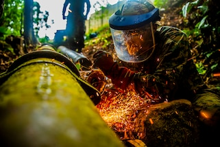 A U.S. Marine begins cutting sections of a broken water pipe in Trujillo, Honduras, Sept. 19, 2018.