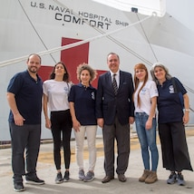 Ambassador Alejandro Daneri, president, White Helmets Commission of Argentina, poses for a group photo with members of the White Helmets Commission of Argentina in front of USNS Comfort (T-AH 20).