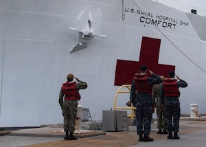 Sailors salute the ensign of the U.S. Navy hospital ship USNS COMFORT before it's scheduled deployment.