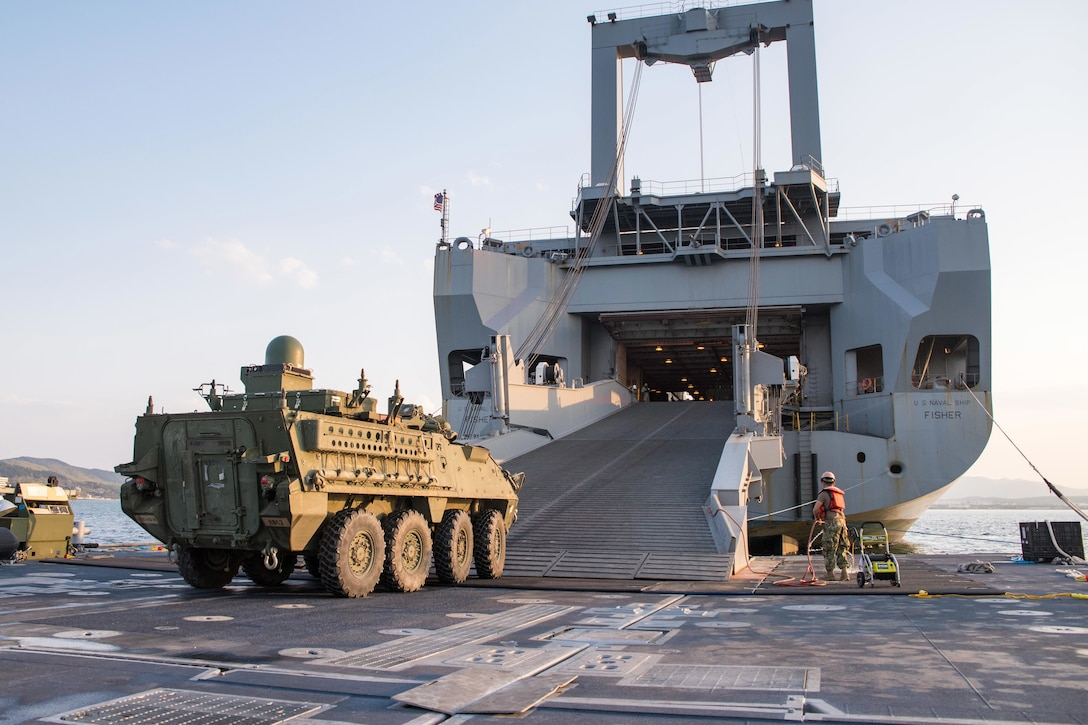 A tactical vehicle drives onto a ship's ramp.