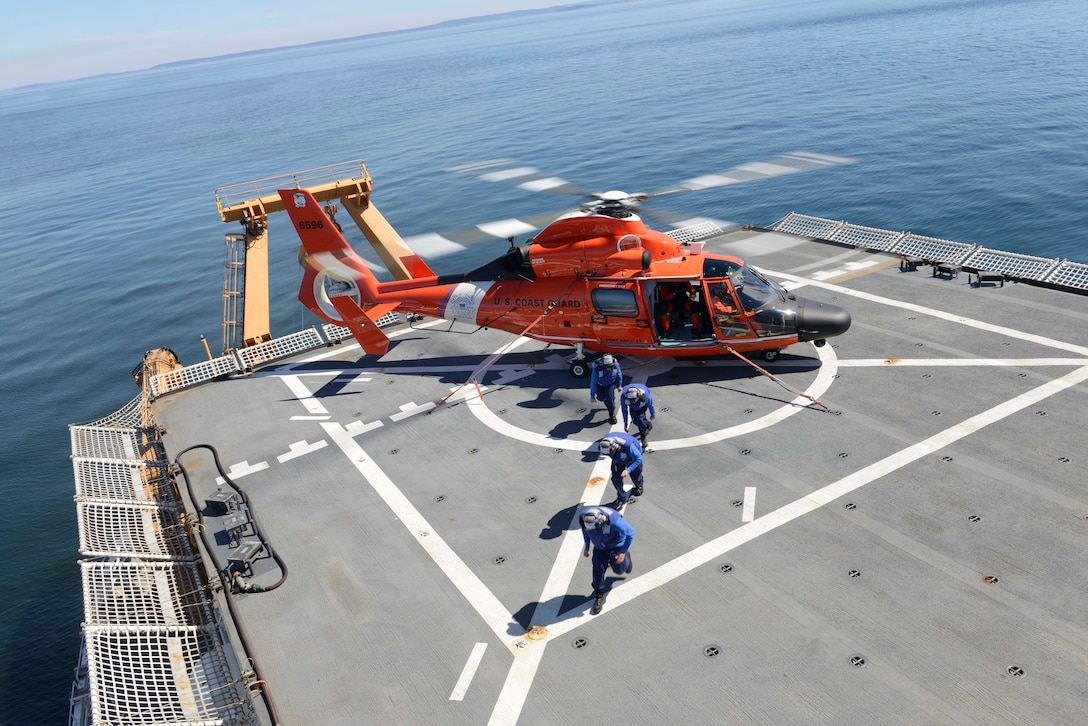 Crew members run from a helicopter on a ship's flight deck.
