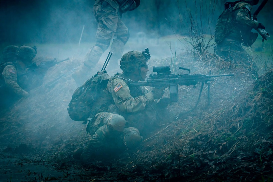 A soldier sits behind a hill and aims a weapon amid blueish smoke.